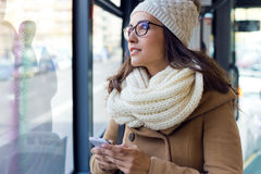Junge Schönheit, die ihren Handy auf einem Bus verwendet Lizenzfreies Stockfoto