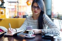 Junge Schönheit, die ihren Handy im Kaffee verwendet Stockbild