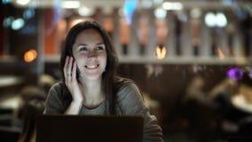 Junge Schönheit, die im Café sitzt und am Telefon spricht Weibliches Arbeiten des Brunette an Laptop-Computer am Abend stock footage