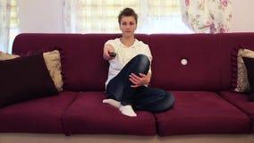 Junge Schönheit, die im Sofa und aufpassendem Fernsehen sitzt stock video