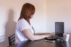 Junge Schönheit, die an Laptop mit dem Tasse Kaffee, smar arbeitet Stockfotografie