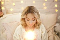 Junge Schönheit, die mit brennenden Kerzen in ihren Händen durch den Weihnachtsbaum sitzt Stockfoto