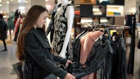 Junge Schönheit, die neue Kleidung in einem Speichersupermarkt sich findet stock video