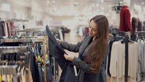 Junge Schönheit, die neue Kleidung in einem Speichersupermarkt sich findet stock footage