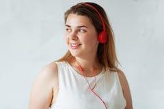 Junge Schönheit, die rote Kopfhörer trägt lizenzfreies stockbild