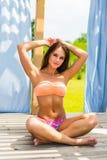 Junge Schönheit, die Sommerferien genießt Schöne junge Frau, bei der Entspannung im Klappstuhl nahe dem Pool Unkosten übergibt lizenzfreies stockfoto