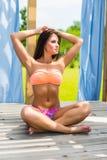 Junge Schönheit, die Sommerferien genießt Schöne junge Frau, bei der Entspannung im Klappstuhl nahe dem Pool Unkosten übergibt stockfoto