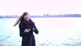 Junge Schönheit, die Tablette nahe See verwendet stock video