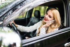 Junge Schönheit, die Telefon beim Fahren des Autos auf Straße nennt Stockfotos