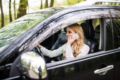 Junge Schönheit, die Telefon beim Fahren des Autos auf Straße nennt Stockfotografie