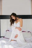 Junge Schönheit, die zu Hause auf Bett sitzt Stockfotografie