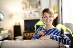 Junge Schönheit, die zu Hause auf einem Sofa fernsieht Lizenzfreies Stockbild