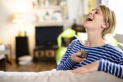 Junge Schönheit, die zu Hause auf einem Sofa fernsieht Lizenzfreies Stockfoto