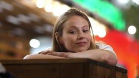 Junge Schönheit, die zur Kamera liegt auf einer Tabelle lächelt stock video footage