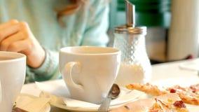 Junge Schönheit in einem Restaurant Pizza essend und Tee trinkend stock video