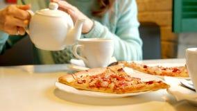 Junge Schönheit in einem Restaurant Pizza essend und Tee trinkend stock video footage