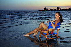 Junge Schönheit im blauen Bikini, der im Stuhl sich entspannt auf dem Ozean sitzt Stockfotografie