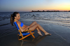 Junge Schönheit im blauen Bikini, der im Stuhl sich entspannt auf dem Ozean sitzt Lizenzfreies Stockbild