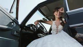 Junge Schönheit im Hochzeits-Kleid, das im Weinlese-Auto aufwirft stock video