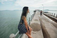 Junge Schönheit im Kleid, das auf dem Pier sitzt und mit Hintergrund des blauen Himmels und des Meeres sich entspannt Lizenzfreies Stockfoto