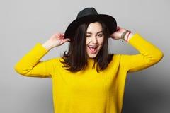 Junge Schönheit im schwarzen Hut und im gelben Pullover Stockfotos