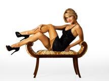 Junge Schönheit im schwarzen Kleid, welches das Sitzen auf einem Stuhl aufwirft Lizenzfreie Stockbilder