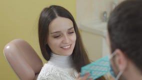 Junge Schönheit im zahnmedizinischen Stuhl Nach dem Verfahren schaut sie im Spiegel Das Konzept eines gesunden Lächelns stock footage