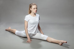 Junge Schönheit macht Übungen auf grauem Hintergrund Lizenzfreie Stockfotografie