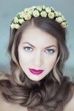 Junge Schönheit mit Blumen im Haar und in den blauen Augen Lizenzfreie Stockbilder