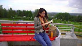 Junge Schönheit mit Brillen ein Buch lesend, das auf einer Bank draußen in einem Park im Sommer sitzt 4 K stock video