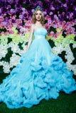 Junge Schönheit mit dem langen blonden Haar im eleganten dunkelblauen Kleid, das am Blumenhintergrund aufwirft Stockfoto