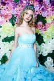 Junge Schönheit mit dem langen blonden Haar im eleganten dunkelblauen Kleid, das am Blumenhintergrund aufwirft Stockbild