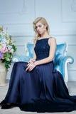 Junge Schönheit mit dem langen blonden Haar im eleganten dunkelblauen Kleid, das am weißen Studio aufwirft Stockfoto