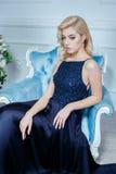 Junge Schönheit mit dem langen blonden Haar im eleganten dunkelblauen Kleid, das am weißen Studio aufwirft Lizenzfreie Stockfotografie