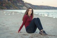 junge Schönheit mit dem langen Haar, in den schwarzen Jeans und roten im Hemd, sitzend auf Sand auf Strand unter Seemöwenvögeln Stockfotos