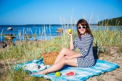 Junge Schönheit mit Picknickkorb auf dem Strand Lizenzfreies Stockbild