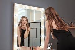 Junge Schönheit nahe Spiegel im Raum Stockbilder