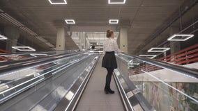 Junge Schönheit steigt auf eine gerade Rolltreppe stock footage