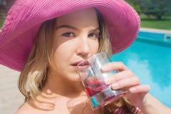 Junge Schönheit trinkendes cocktai nahe Swimmingpool Lizenzfreie Stockbilder