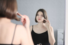 Junge Schönheit tut Make-up und schaut im Spiegel Stockbild