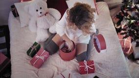 Junge Schönheit wickelt Weihnachtsgeschenke beim Sitzen auf Bett im Schlafzimmer ein Beschneidungspfad eingeschlossen stock video footage