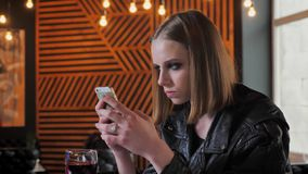 Junge Schönheiten in der schwarzen Jacke mit schwerem bilden das Simsen am Telefon, konzentriert, Caféhintergrund stock video footage