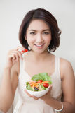 Junge Schönheiten des Lächelns, die eine Schüssel Salat halten stockbild