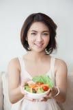 Junge Schönheiten des Lächelns, die eine Schüssel Salat halten lizenzfreie stockfotografie