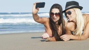 Junge Schönheiten, die Fotos auf Strand machen Stockfoto