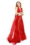 Junge Schönheits-Frau in flatterndem rotem Kleid Stockfotos