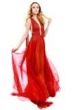 Junge Schönheits-Frau in flatterndem rotem Kleid Stockfoto