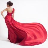 Junge Schönheits-Frau in flatterndem rotem Kleid Weißer Hintergrund lizenzfreie stockfotos