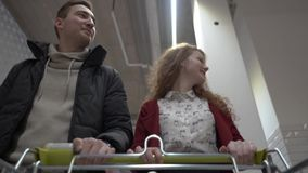 Junge Schönheits- und Mannwege durch den Supermarkt Ansicht vom Einkaufswagen stock video
