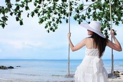Junge Schönheitsdame, die auf Seilschwingen sitzt Lizenzfreies Stockfoto